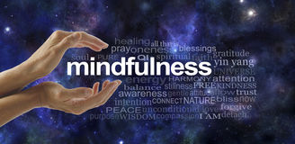 Mindfulness Meditation Word Cloud. Side view of female cupped hands with the word MINDFULNESS between surrounded by a relevant word cloud on a dark blue deep Royalty Free Stock Photography