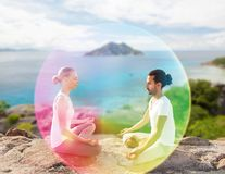 Couple doing yoga in lotus pose with rainbow aura royalty free stock photo