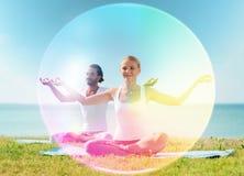 Couple doing yoga in lotus pose with rainbow aura stock photos