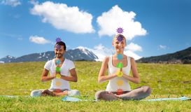Couple doing yoga in lotus pose with seven chakras royalty free stock photos