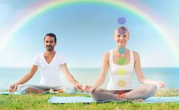 Couple doing yoga in lotus pose with seven chakras royalty free stock images
