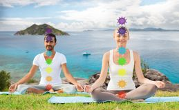 Couple doing yoga in lotus pose with seven chakras stock photos