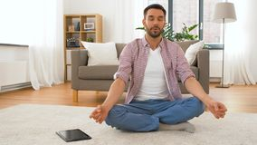 Man with tablet computer meditating at home royalty free stock image