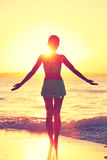 Mindfulness woman practicing yoga sun salutation at beach morning sunrise. Silhouette of fit person standing in sun flare raising arms to the sky with an open Royalty Free Stock Photography