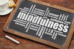Mindfulness word cloud. On a vintage slate blackboard with a cup of coffee and cookie Stock Image