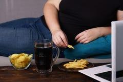 Mindless snacking och att äta för mycket, brist av fysisk aktivitet royaltyfri foto