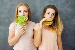 Two young women with salad and hamburger stock images