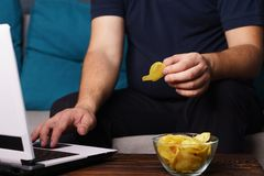 Mindless snacking, overeating, laziness, homebody. Mindless snacking, overeating, lack of physical activity, laziness, homebody. fat overweight man engrossed in royalty free stock photo