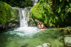 MINDO, ECUADOR - AUGUST 27, 2017: Unidentified people swiming near of the beautiful waterfall in green forest with. Stones in river at Mindo, Pichincha Stock Images