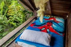 MINDO, ECUADOR - JUNE 27, 2015: Bed in La Casa de Cecilia hostel in Mindo villag stock photo