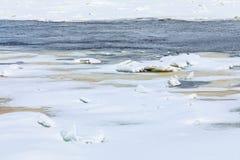Mindre kulle och isflaken på vinterfloden arkivfoton