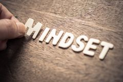 Mindset Wood Letters. MINDSET, closeup hand place a wood letter into the word for mindset concept stock photography