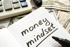 Mindset dei soldi scritto a mano nelle banconote del dollaro e di una nota Immagini Stock