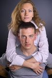 He is mine. Family portrait of a young and happy couple where girl embrassing her boyfriend Royalty Free Stock Images