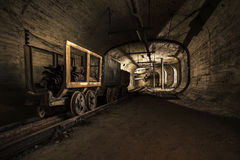 Mine cart. Abandoned coalmine with a mine cart on the tracks royalty free stock photos