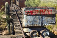 Mine Cart with danger trestle sign on Rail Tracks. Mine Cart with Red Paint Danger Trestle Sign on Old Rusted Rail Tracks next to Saguaro Cactus in Arizona stock photography