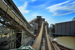 Mine with conveyor belts. Conveyor belts and mine with clouds and sky in background royalty free stock photography