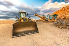 Excavator and stone crusher in a quarry royalty free stock photos
