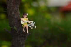 Mine postacie bawić się gitarę dziewczyna na drzewnych bagażnikach podczas gdy siedzący fotografia stock