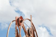 Mine shaft pulley from a low angle with sky and clouds behind stock photos