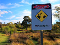 Mine shafts danger sign. An Australian warning sign to watch out for mine shafts in this park landscape at Hill End - a former gold-mining town Stock Images