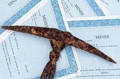 Mine stock certificates with rusted pick. Wrought iron antique pick axe with many mining stock certificates royalty free stock images