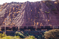 Mine train. A train passes along the tracks next to a heap of disused sand from mining operations near Upington in South Africa stock photos