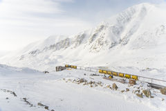 Mine wagons. Yellow mining trolleys on rails with snow mountains on a background Stock Photography