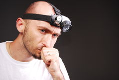 Mine worker. Portrait of a mine worker thinking on a gray background Royalty Free Stock Photography