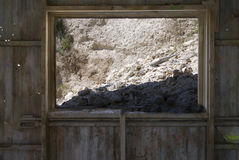 Mined Diatomaceous Earth in Abandoned Mine. Mined diatomaceous Earth falling through the window of an old abandoned mine Royalty Free Stock Image