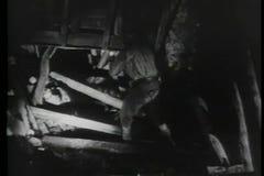 Mineiros com lanternas elétricas que verificam dano no túnel filme