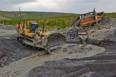 Minería aurífera en Susuman La niveladora y el derocker foto de archivo