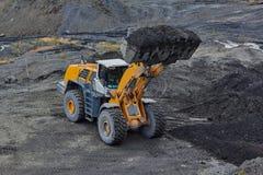 Minería aurífera en Susuman Un auto-cargador con una cucharón llena foto de archivo