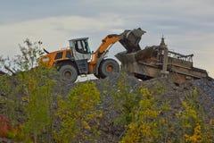 Minería aurífera en Susuman Un auto-cargador y un de-eje de balancín imagen de archivo