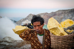 Miner carying baskets of sulphur at Kawah Ijen crater, Indonesia Royalty Free Stock Photography
