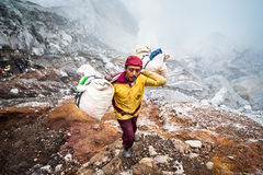 A miner at Kawah Ijen carries sulpher out of the crater Stock Photos