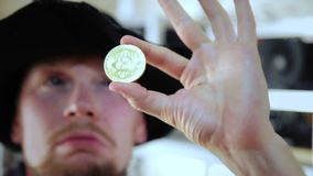 Man looking and checks the coin for authenticity