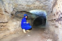 Miner man underground in a mine tunnel.  Worker in overalls, safety helmet Royalty Free Stock Photo