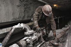 Miner in a mine. Miner performs work in a mine Stock Photo