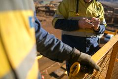 Worker looking at personnel risk assessment take five book at construction. Miner worker looking at personnel risk assessment take five book at construction mine royalty free stock images