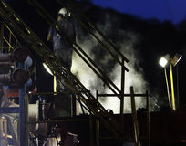 Miner working at rig. Worker is working on the rig and some steam is coming up Stock Image
