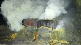 Mineração crua do enxofre na cratera do vulcão ativo de Kawah Ijen em Java imagem de stock