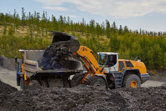 Minería aurífera en Susuman El auto-cargador carga un camión del descarga-cuerpo de la carrera El área de Magadan Kolyma IMG_1006 Imagen de archivo libre de regalías