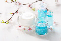 Mineral bath salts, cream, shower gel and flowers on the wooden table. Royalty Free Stock Image