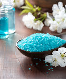 Mineral bath salts, shower gel, towels and spring flowers. Spa concept. Mineral bath salts, shower gel, towels and spring flowers on the wooden table Royalty Free Stock Photos