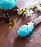 Mineral bath salts, shower gel, towels and spring  flowers on the wooden table. Stock Image