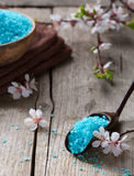 Mineral bath salts,  towels  and flowers on the old wooden table Royalty Free Stock Photos