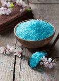 Mineral bath salts, towels and flowers on the old wooden table. Royalty Free Stock Photo