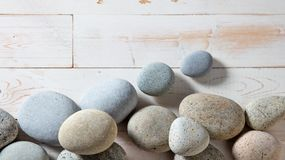Mineral border of pebbles for mindfulness or spirituality, flat lay. Pure mineral border of grey zen stones and pebbles set on white wooden background for Royalty Free Stock Image