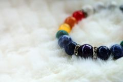 Mineral Chakra color luck fortune stone bracelet on white wool background. Amulet accessories for good good lucky fortune and happy life Royalty Free Stock Photos